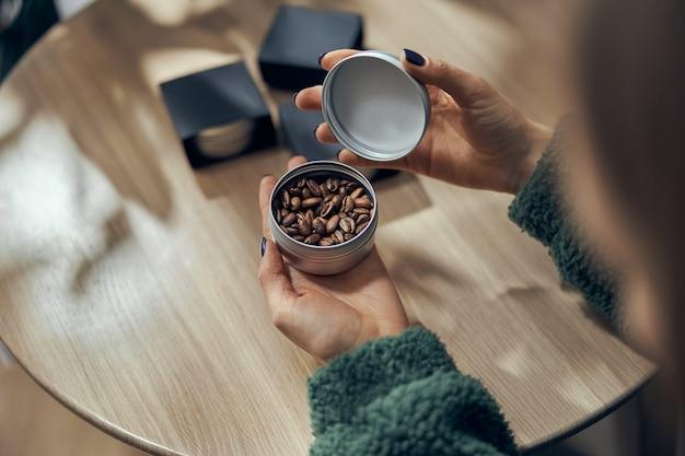 Weibliche hand hält schüssel gemahlenen kaffee und bohnen in geschenkbox auf dem tisch.