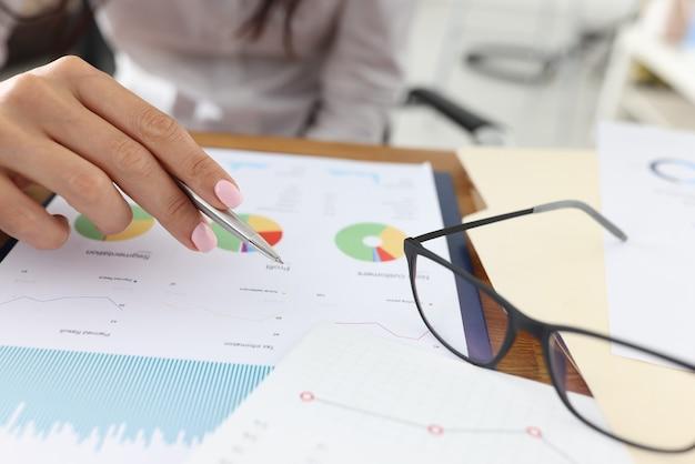 Weibliche hand hält stift für kommerzielle charts neben brille liegen
