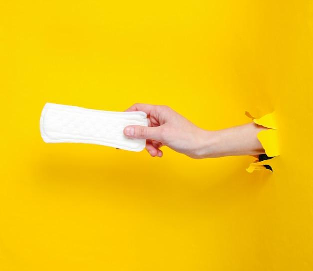Weibliche hand hält tägliche damenbinde durch zerrissenes gelbes papierloch. minimalistisches modekonzept
