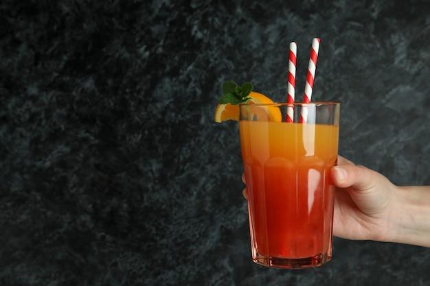 Weibliche hand hält tequila-sonnenaufgang-cocktail auf schwarzem, rauchigem hintergrund