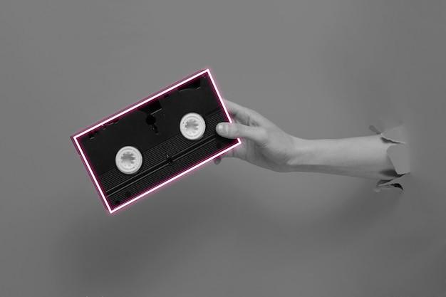 Weibliche hand hält videokassette mit neonrahmen durch zerrissenes papier