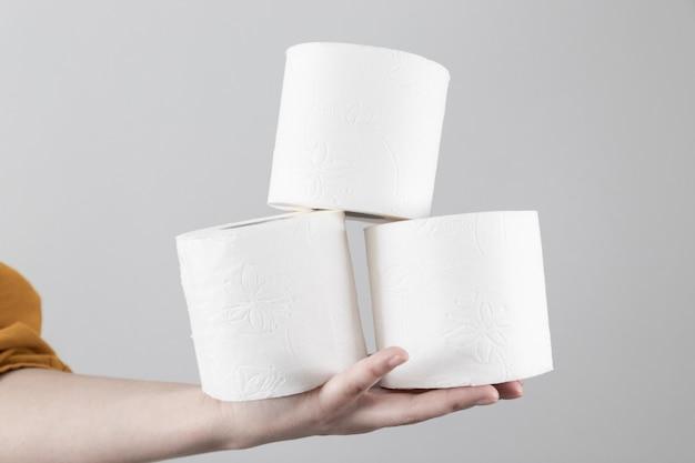 Weibliche hand hält weiche toilettenpapierrollen auf grau