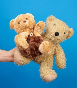 Weibliche hand halten einen kleinen braunen spielzeug-teddybär auf einem blauen hintergrund