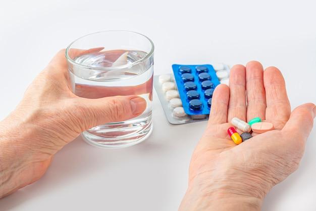 Weibliche hand halten handvoll verschiedener pillen und glas für wasser. gesundheitswesen und medizin für ältere menschen. arzneimittel zur behandlung von krankheiten alter älterer menschen. wechseljahre oder hormonelles medikament für frauen