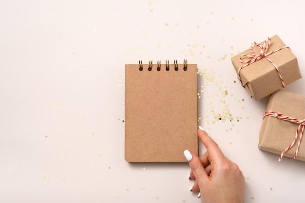 Weibliche hand halten notizbuch leeres papiermodell, goldene sterne konfetti, geschenkboxen auf beigem hintergrund. flache lage, draufsicht, kopierraum, minimalistisch. weihnachten zusammensetzung des neuen jahres.