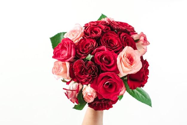 Weibliche hand halten rosa und rote rosenblumenstrauß lokalisiert auf weiß