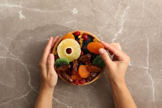 Weibliche hand halten schüssel mit getrockneten früchten auf grau