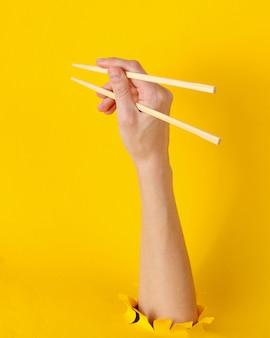 Weibliche hand halten stäbchen durch zerrissenes loch auf gelb. minimalistisches lebensmittelkonzept. draufsicht