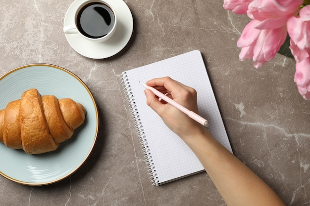 Weibliche hand halten stift auf grauem hintergrund mit notizbuch, kaffee, tulpen und croissant, draufsicht