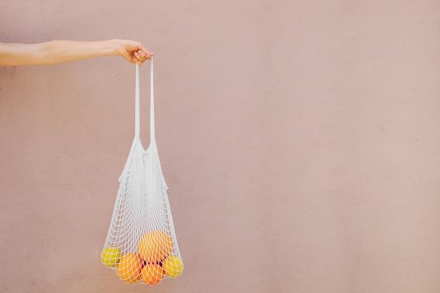 Weibliche hand halten wiederverwendbare netzbeutel mit früchten. nachhaltiger lebensstil. plastikfreies konzept.