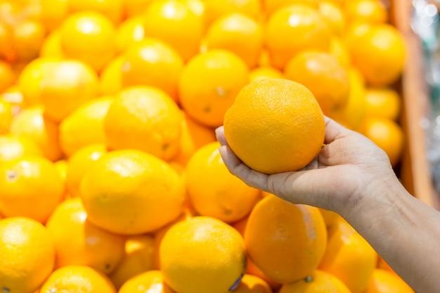 Weibliche hand heben orange im supermarkt auf