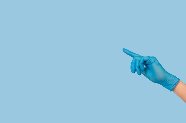 Weibliche hand im blauen medizinischen chirurgischen handschuh, der auf etwas gegen hellblauen hintergrund zeigt