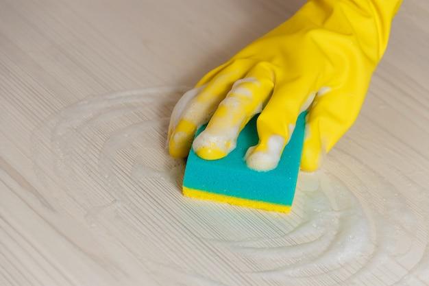 Weibliche hand im gelben handschuh, der helle hölzerne moderne tabelle säubert