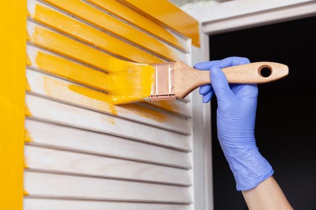 Weibliche hand im gummihandschuh mit bürstenmalereiholztür mit gelber farbe