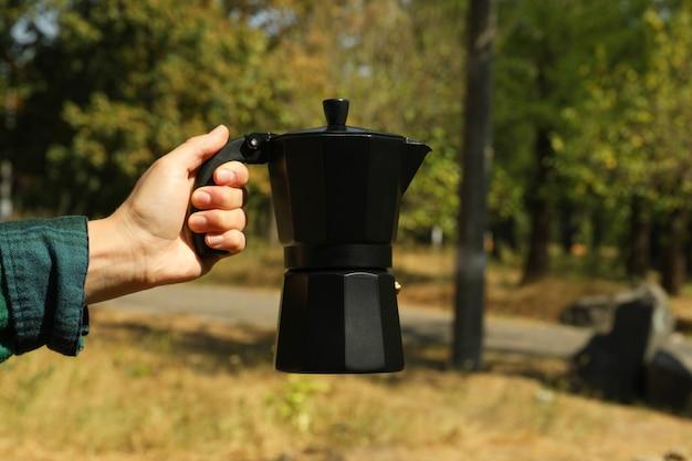Weibliche hand im hemd halten kaffeemaschine im freien