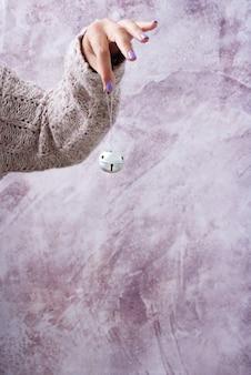Weibliche hand im kuscheligen rosa pullover, der eine klingelglocke hält. weihnachtsdekoration konzept