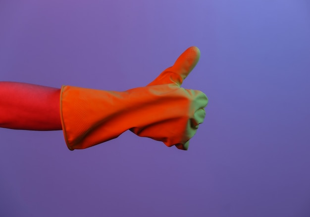 Weibliche hand im latexhandschuh zeigt daumen nach oben. neonlicht mit farbverlauf