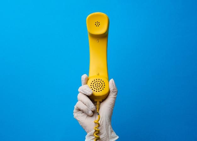 Weibliche hand im medizinischen handschuh, der gelben telefonlautsprecher hält