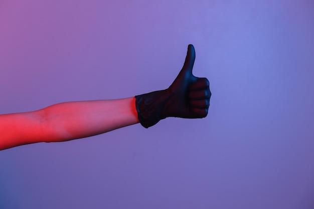 Weibliche hand im schwarzen latexhandschuh zeigt daumen nach oben. neonlicht mit farbverlauf