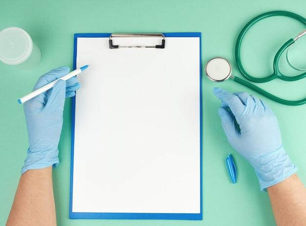 Weibliche hand in blauen sterilen handschuhen und medizinischem stethoskop,