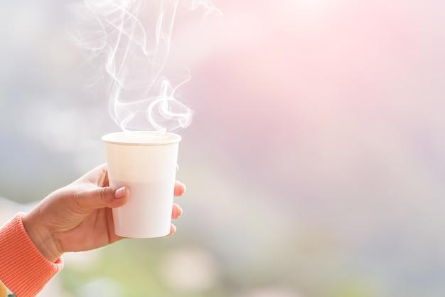Weibliche hand in den handschuhen, die schale mit heißem tee oder kaffee halten. teepause