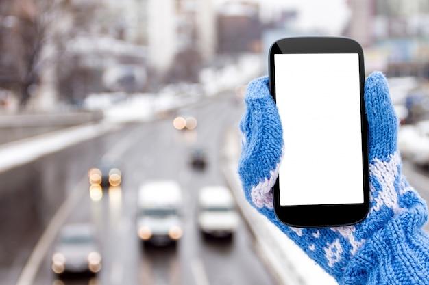 Weibliche hand in den handschuhen mit telefon im städtischen szenenhintergrund