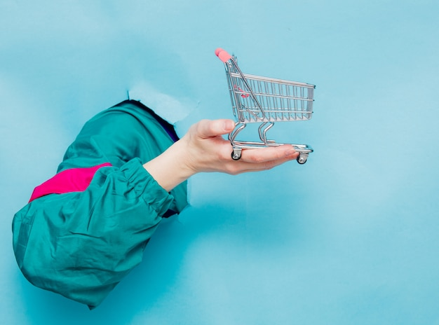 Weibliche hand in der jacke der art 90s, die supermarktwarenkorb hält