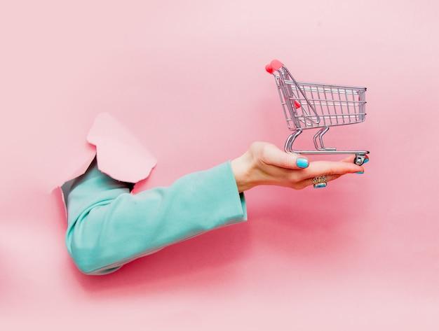 Weibliche hand in der klassischen blauen jacke mit einkaufswagen