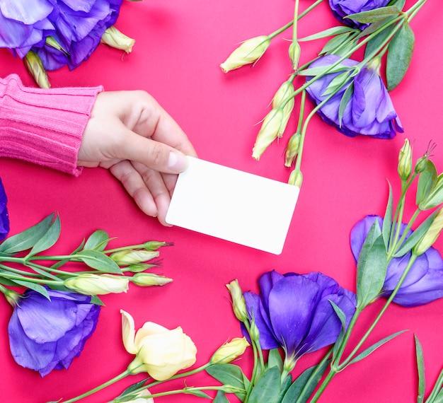 Weibliche hand in der rosa strickjacke, die eine leere weißbuchvisitenkarte hält