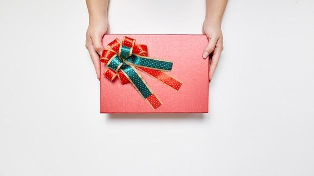 Weibliche hand in der strickjacke, die einen roten geschenkkasten für weihnachten, neues jahr, valentinsgruß mit c hält