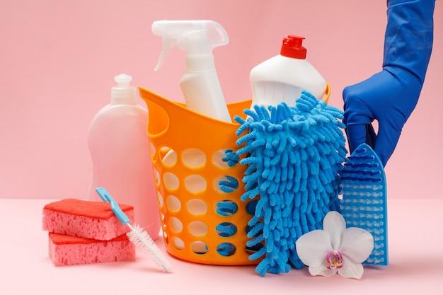 Weibliche hand in einem gummihandschuh mit flaschen spülmittel, glas- und fliesenreiniger, reinigungsmittel für mikrowellenherde und herde, lappen, bürsten und schwämme. wasch- und reinigungsset.