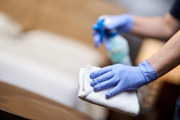 Weibliche hand in einem handschuh mit einem weißen putzlappen in einem hotelzimmer. platz kopieren. hauswirtschafts- und hygienekonzept