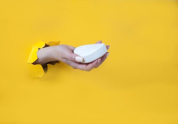 Weibliche hand in einem loch auf gelb hält eine weiße seife
