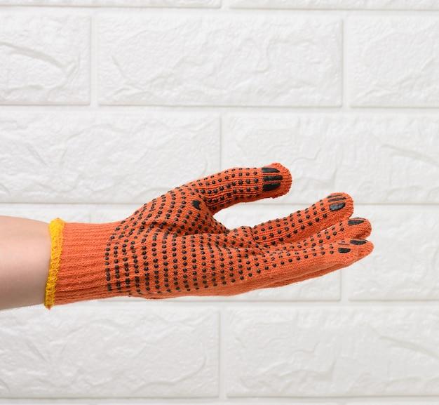 Weibliche hand in einem orangefarbenen arbeitsschutzhandschuh vor dem hintergrund einer weißen backsteinmauer, die hand hält bedingt ein objekt