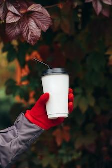 Weibliche hand in einem roten handschuh, der einen weißen kaffeebecher mit strohhalm auf dem hintergrund von weinblättern hält