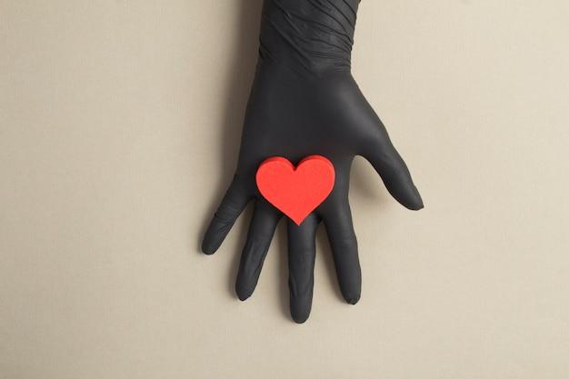 Weibliche hand in einem schwarzen handschuh mit rotem herzen auf dem grauen hintergrund