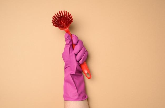 Weibliche hand in lila gummihandschuhen hält eine plastikreinigungsbürste auf einem beigen hintergrund, kopie spce