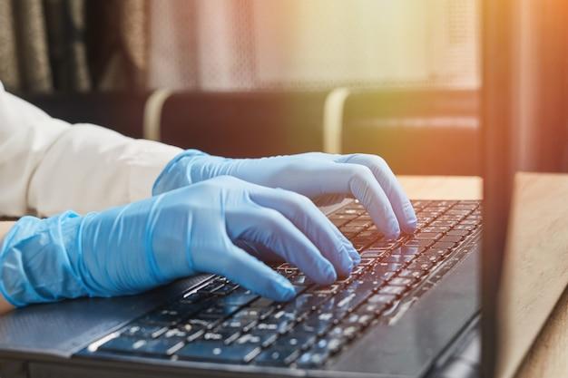Weibliche hand in schutzhandschuhen, die auf laptop-tastatur tippen. schutz vor coronavirus covid-19 an öffentlichen orten.