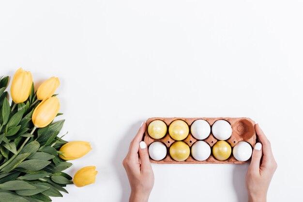 Weibliche hand legt auf dem tisch ein tablett mit ostereiern neben den gelben tulpen