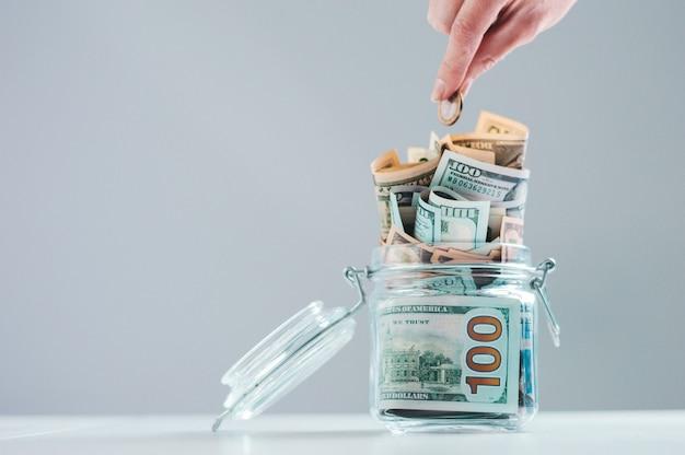 Weibliche hand legt eine münze in ein glas sparschwein voller geld.
