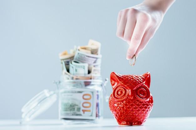 Weibliche hand legt eine münze in form einer eule in ein sparschwein