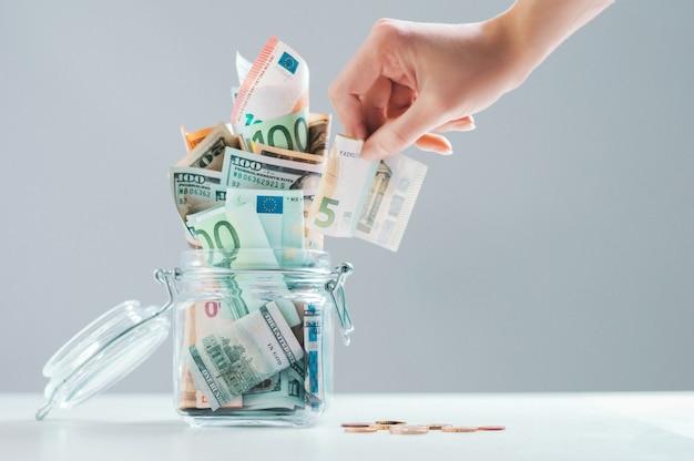 Weibliche hand legt eine rechnung in ein sparschwein aus glas voller geld