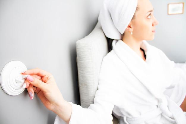 Weibliche hand macht das licht aus. eine schöne frau macht das licht an.