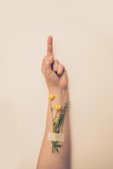 Weibliche hand mit blumen auf ihrem handgelenk, das mittelfingergeste zeigt
