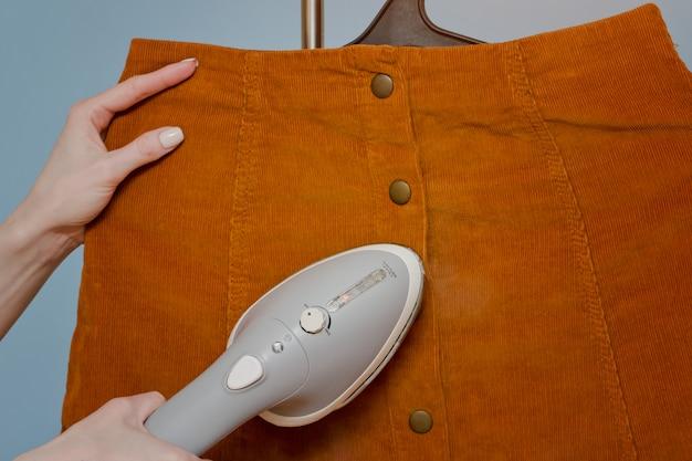 Weibliche hand mit dampfbügeleisen, nahaufnahme