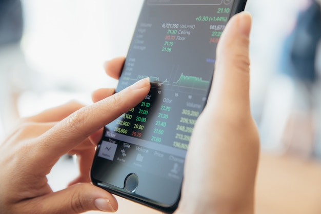 Weibliche hand mit dem smartphone, der online aktien in der kaffeestube, geschäftskonzept handelt