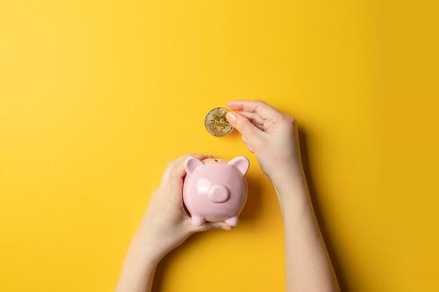 Weibliche hand mit der bitcoin münze setzte sich in ein sparschwein