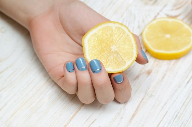 Weibliche hand mit der hellblauen nagelkunst, die zitrone hält.
