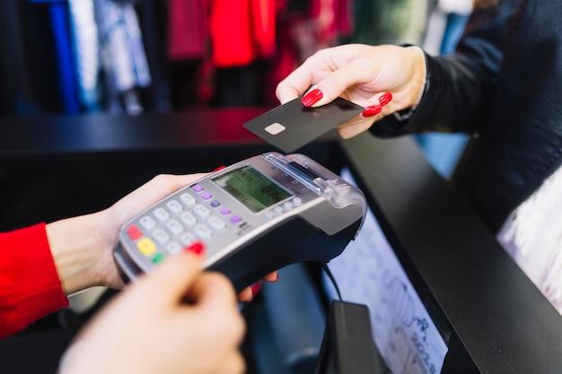 Weibliche hand mit der kreditkarte, die durch terminal für die zahlung im shop bezahlt