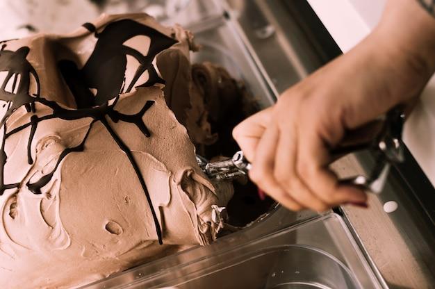 Weibliche hand mit der schaufel, die eiscreme nimmt